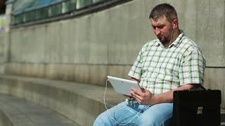 Businessman communicates via tablet computer. Man with tablet pc communicates through videochat. Fat man in checkered shirt with briefcase holds in hands tablet pc with earphones