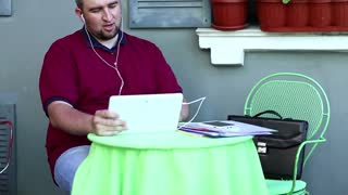 Businessman in cafe talks via tablet computer. Fat man sits at the table in summer restaurant and speaks on tablet pc, smartphone and business papers lies on the table