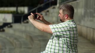 Businessman sits and records videos on smartphone. Fat man makes photos on his cell phone