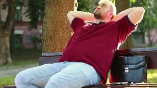 Businessman sits on bench in city park and rests. Man relaxes after hard working day