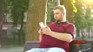 Businessman sits on the bench and records videos on smartphone. Fat man makes photos on his cell phone