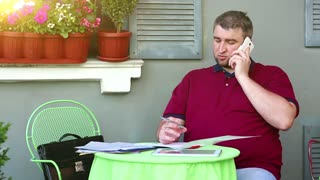 Businessman speaks on smartphone in cafe. Man sits at the table in summer restaurant and speaks on cell phone, tablet computer and business papers lies on the table