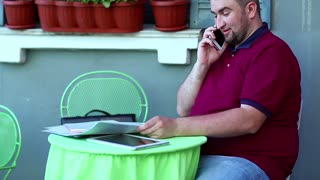 Businessman talks on smartphone in cafe and works with business papers. Man sits at the table in summer restaurant and speaks on cell phone, tablet computer lies on the table