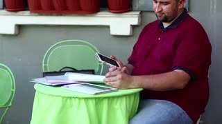 Businessman talks on smartphone in cafe and works with business papers. Man sits at the table in summer restaurant and speaks on cell phone, tablet pc lies on the table