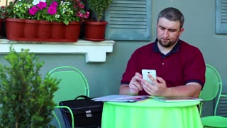 Businessman uses smartphone in cafe. Man sits at the table in summer cafe and works with smartphone. Entrepreneur holds in hands his cell phone, business papers are on the table