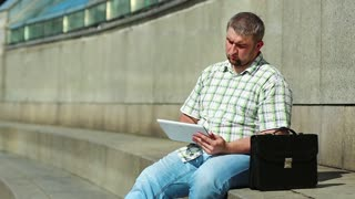 Businessman works with his tablet computer. Man with briefcase sits on big concrete steps and uses tablet pc