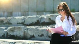 Businesswoman in glasses with commercial papers. Young career woman sits on the big stairs in downtown and holds in hands business documents