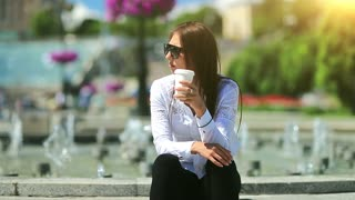 Businesswoman sits near fountains and drinks coffee. Young attractive woman in sunglasses with cup of tea in hand. Woman drinks coffee in Kiev city centre, Ukraine, beautiful sun at background
