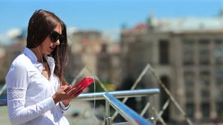 Businesswoman uses smartphone. Pretty woman with long hair in sunglasses with red mobile phone in the Kiev city, Ukraine