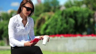 Businesswoman with red cell phone drinks coffee. Girl in sunglasses with smartphone