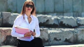 Businesswoman with works papers looks at the camera. Young career woman holds in hands business documents
