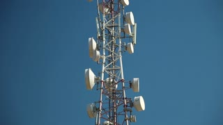 Cell phone telecommunication tower. Communication tower antenna on blue background. Antennas of mobile phone communication, television, internet, radio, on blue sky background