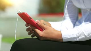 Close-up of woman hands with french manicure with red smartphone. Female with smartphone. Businesswoman with mobile phone. Woman types sms on smartphone