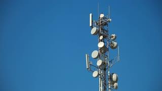 Communication tower antenna on blue background. Cell phone telecommunication tower. Antennas of mobile phone communication, television, internet, radio, on blue sky background
