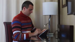Concentrated man with tablet pc sits at the table. Man sits on chair at the table in hotel room and uses tablet computer