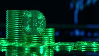 Crypto currency Gold Bitcoin, BTC, Bit coins rotates. Block chain technology, Bitcoin mining concept in green style, monitor with financial charts at background