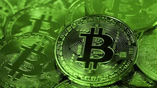 Cryptocurrency Bitcoin, BTC, coins rotates in green light. Blockchain technology, bitcoin mining concept, macro shot of bitcoins