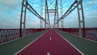 Cyclist rides over the bridge, video shooting with an action camera on a bicycle. Bicyclist rides on the pedestrian bridge in Kiev, Ukraine