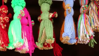Dolls made of threads in souvenir shop. Colorful dolls hanging on strings