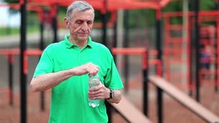 Elderly athlete on outdoor gym drinks water. Active elderly athlete in green t-shirt training in outdoor gym