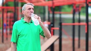 Elderly athlete on outdoor gym drinks water. Active elderly athlete in green t-shirt training in outdoor gym