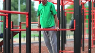 Elderly grey-haired sportsman doing physical exercise on sports ground. Active elderly athlete in green t-shirt trains in open air gym. Aged grey-haired man doing strenuous exercise on parallel bars
