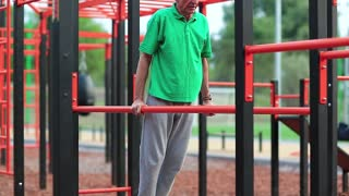 Elderly grey-haired sportsman makes physical exercise on sports ground. Active elderly athlete in green t-shirt trains in open air gym. Aged grey-haired man makes strenuous exercise on parallel bars