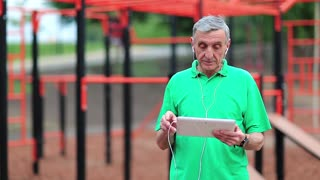 Elderly grey-haired sportsman uses tablet computer at sport ground. Senior man stands near sports ground and holds in hands tablet pc