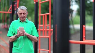 Elderly sportsman stands near sports ground and uses smartphone. Senior man works with his cell phone. Grey-haired active athlete stands near outdoor gym and holds in hands mobile phone