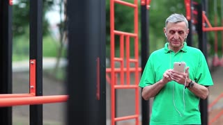 Elderly sportsman uses smartphone on sports ground. Senior man works with his cell phone. Grey-haired active athlete stands near outdoor gym and holds in hands mobile phone