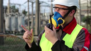 Electrician in respirator with portable radio transmitter on electric power station. Power engineering specialist in gas mask, goggles and hard hat on heat power plant communicates via radio station