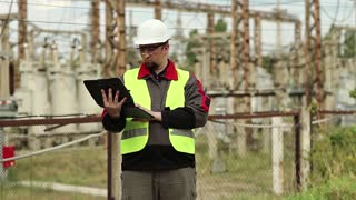 Electrician with computer on power station.  Factory worker with tablet pc. Worker in hard hat at electric power plant, engineering supervision