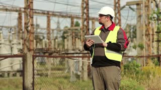 Electrician with computer on power station. Worker in hard hat at electric power plant, engineering supervision. Factory worker with tablet pc