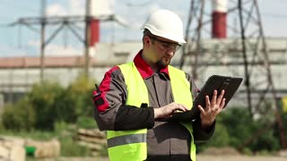 Engineer with personal computer at power station. Power engineering specialist with pc at heat electric power station. Worker in hard hat at heat electric power station, engineering supervision