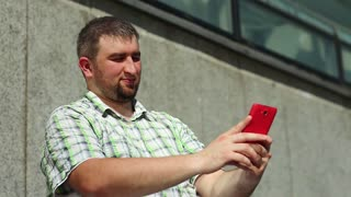 Fat funny man makes selfie on red smartphone. Guy makes photos on cell phone