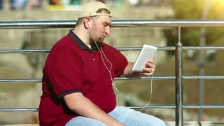 Fat man communicates via tablet computer. Man with tablet pc communicates through videochat. Businessman in baseball cap holds in hands white tablet pc with earphones