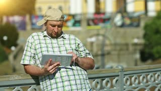 Fat man in baseball cap uses tablet computer. Guy in checkered shirt works with his tablet pc, beautiful sun at background