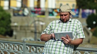 Fat man in baseball cap uses tablet computer. Guy in checkered shirt works with his tablet pc in the city