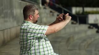 Fat man records video on smartphone. Guy makes photos on cell phone