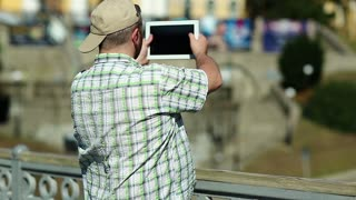 Fat man records video on tablet computer. Guy makes photos on his tablet pc