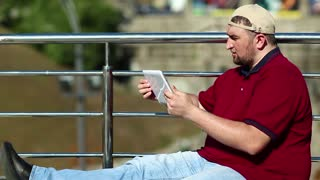Fat man speaks via tablet computer. Man with tablet pc communicates through videochat. Businessman in baseball cap sits and holds in hands white tablet pc
