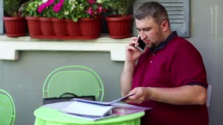 Fat man speaks via tablet pc in cafe. Businessman sits at the table in summer restaurant and speaks on tablet computer, smartphone and business papers lies on the table