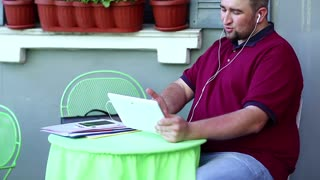Fat man speaks via tablet pc in cafe. Businessman sits at the table in summer restaurant and talks on tablet computer, smartphone and business papers lies on the table