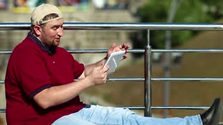 Fat man talks via tablet computer. Man with tablet pc communicates through video chat. Businessman in baseball cap sits and holds in hands white tablet pc