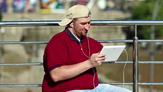 Fat man uses tablet computer. Man with tablet pc sits in the city. Businessman in baseball cap sits and holds in hands white tablet pc