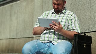 Fat man works with tablet computer. Man with briefcase uses tablet pc with earphones