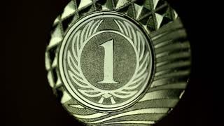 Filst place gold medal. Gold medal, awarded to the winner. Medal for competition winner on black background. 1st place champion medallist