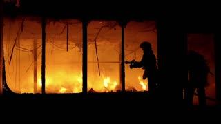 Fire extinguishing, fire brigade inside burning premises. Brave firemen inside burning building. House destroyed by fire