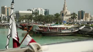 Flag of Qatar on the boat in harbour, islamic cultural center Fanar in old town of Doha, Qatar, Persian Gulf, Arabian Peninsula, Middle East. Doha - capital and most populous city in Qatar