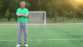Football trainer stands on football field, physical education teacher. Senior man in green t-shirt stands on soccer field and looks at camera